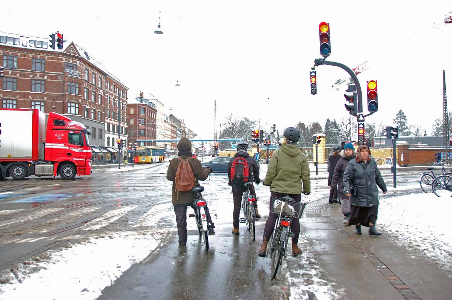 A snowy afternoon on Nørrebrogade in Copenhagen. Bike lights will turn green seconds before car lights to give the cyclists the first right of way. Cyclists feel safe riding in their designated lane.