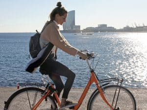 Girl cycling at Bogatell beach in Barcelona