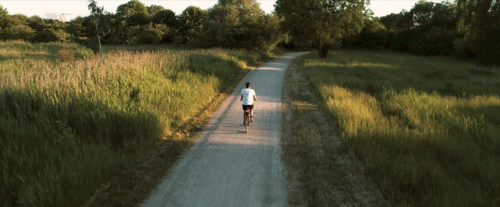 Guy biking green forest Donkey Republic sustainable bike-share