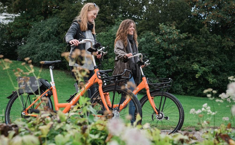 girls happy bike park green Donkey Republic bike-share