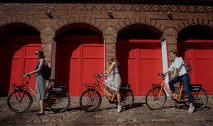 3 girls on 3 orange Donkey Republic bikes in front of red doors