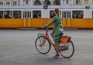 girl on an orange bike by bike-share system Donkey Republic